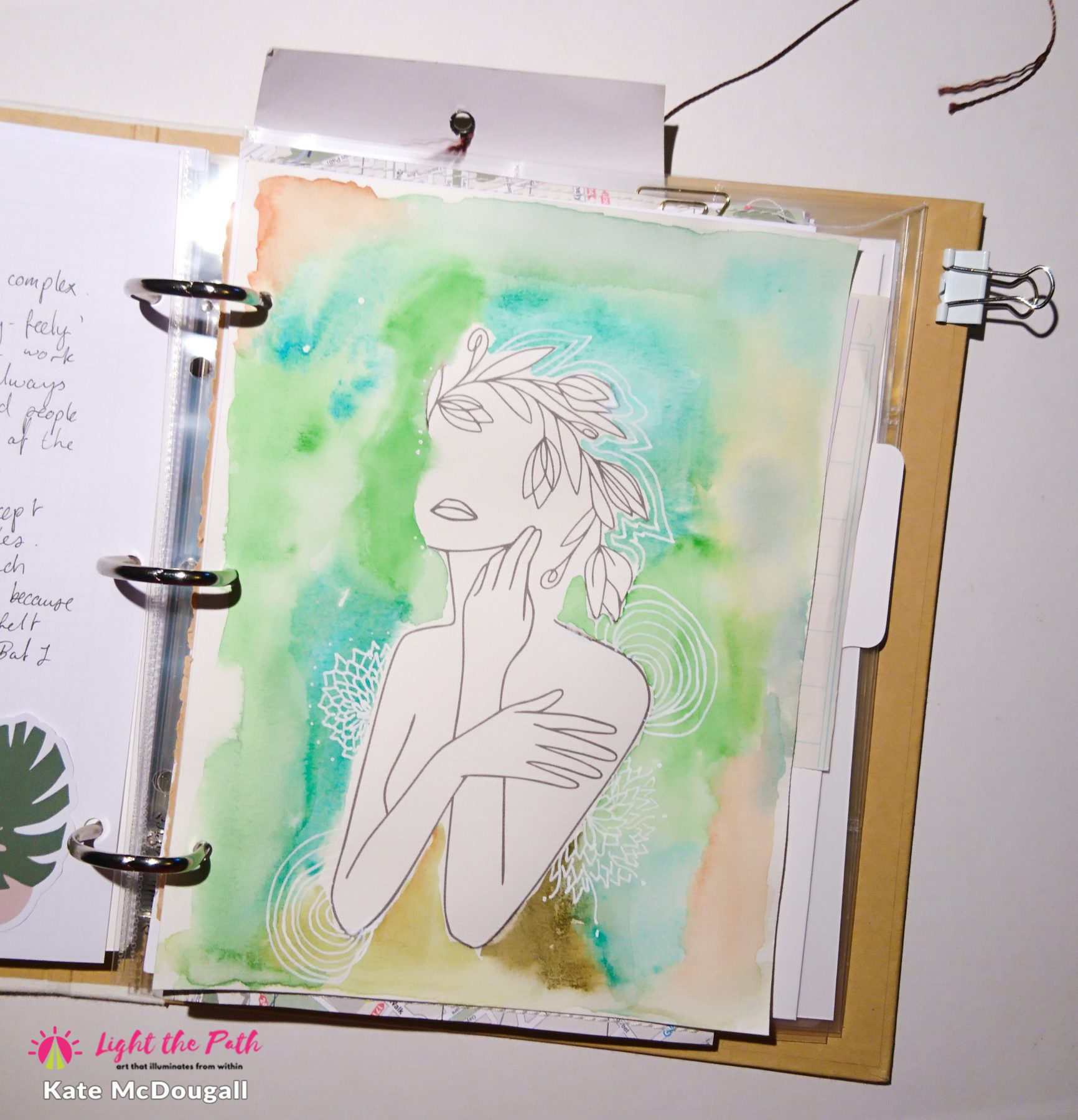 A painted page featuring a line art of a feminine figure, on a background of green and blue watercolour effects.